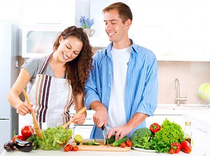 Pareja consciente de la importancia de alimentación y salud, preparando una ensaladas y cortando verduras.