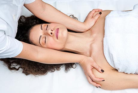 Mujer dándose quiromasaje y sometiéndose a un ajuste de cuello.